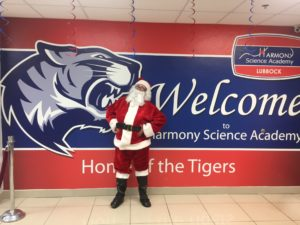 Santa Claus posing in front of the HSA mural in the Foyer.